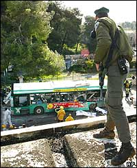 Soldier looks down on wrecked bus