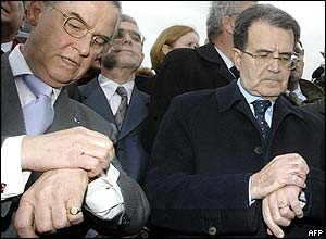 Chairman of the European Commission, Romano Prodi, (centre) checks his watch for the start of the three-minute silence