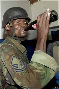Rebel drinks a bottle of Coke in Cap-Haitien police station