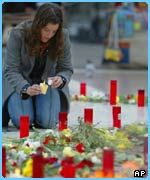 A woman lights a candle in a tribute to the victims