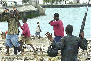 Looters in Cap-Haitien raise their hands as an armed rebel warns off looting