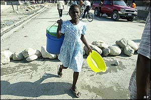 Girl carrying water supplies crosses roadblock made of stones in Port-au-Prince