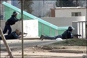 UNMIK police officers take cover near the bridge over the Ibar river, that divides the northern Serb-dominated part from the southern Albanian-dominated part of Mitrovica