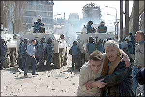 Injured people are led away as UN peacekeepers step in to separate the two sides in the northern town of Mitrovica