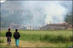 Two young Kosovars walk in a field as several houses burn in Mitrovica
