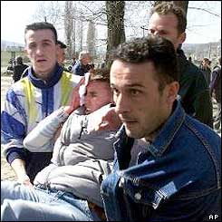 Ethnic Albanians carry away wounded man