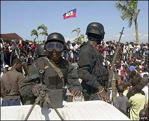 Police watch supporters of Aristide at rally to mark his third anniversary in office, 7 Feb 2004, in Port-au-Prince