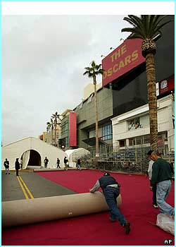 Workers unroll the red carpet in front of the Kodak Theater in preparation for the Oscars. In just a matter of hours, the stars will be working their way down it!