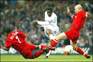 Jay Jay Okocha gets his shot off under pressure from George Boateng and Danny Mills