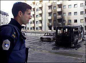A Kosovo police officer looks at burned out car in a mainly Serb neighbourhood of Pristina