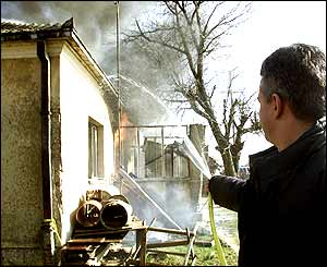 Kosovo Albanian trying to put out a fire at the house of his Serb neighbour in Kosovo Polje