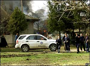 Kosovo policemen in Obilic where Serb-owned houses were burned
