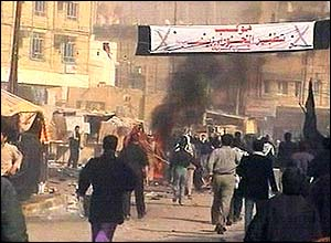 People run on the streets of Karbala as a series of blasts take place