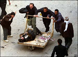 Iraqis use a pushcart to remove a victim