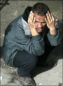 A dazed man looks around at the scene of several bomb blasts