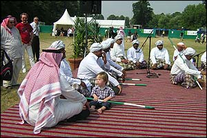 A young boy sitting with the Saudi dance troop who gave a performance to much applause