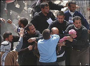 People attack a man (with bald head, partly obscured, centre) suspected of involvement in the blasts