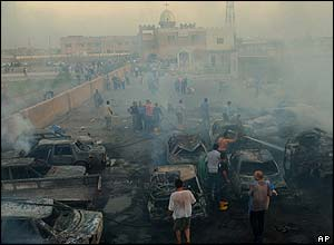 Iraqis survey the scene after a bomb blast near a church in al Doura neighbourhood