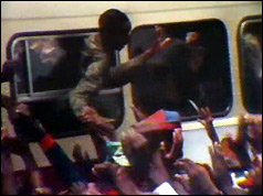 Soldier leans out of bus to shake hands with supporters