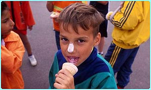 A boy gets ice-cream on his nose