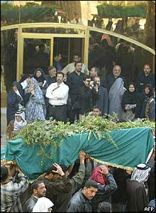 Iraqi mourners carry a coffin during a mass funeral in Karbala