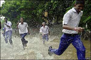 School children run through rainwater in Bombay, India