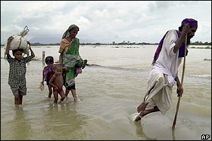 A handicapped man with his family wades through floodwater in Assam