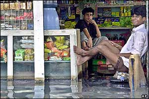 Flood affected shopkeepers sit in a waterlogged shop in Dhaka