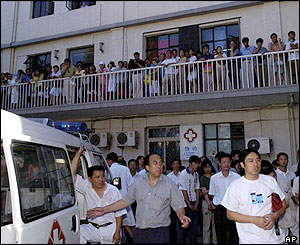An ambulance with onlookers waits in front of the emergency section of No. 1 Hospital of Beijing University, 4/8/04
