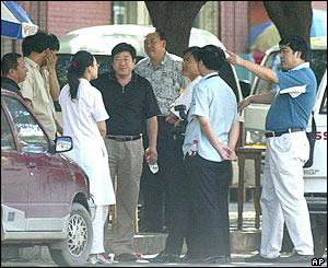 Officials and hospital staff wait outside the kindergarten, 4/8/04