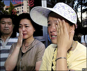 People try to hold back the tears outside the Beijing kindergarten, 4/8/04