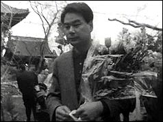 A man carries flowers at the funeral for the Japanese victims
