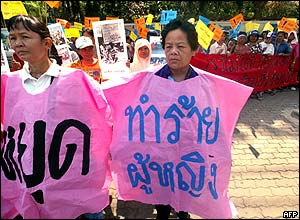 Two Thai women wear banners in a parade near the Parliament House in Bangkok.