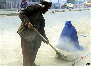 An Afghan man sweeps around a woman begging on the streets of Kabul