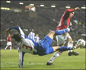 Ruud Van Nistelrooy avoids a high tackle from Pedro Emanuel