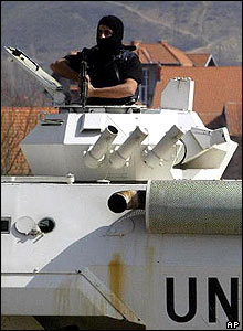 Armed UN police officer watches from tank turret in city of Mitrovica