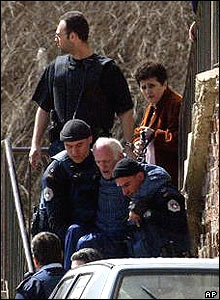 UN police officers carry disabled Serb man from his home in Mitrovica