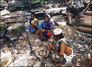 Three women sit in the midst of debris at Alang