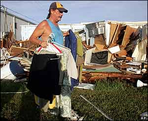 Dan Strong removes clothing from his mobile home in Punta Gorda a day after Charley struck