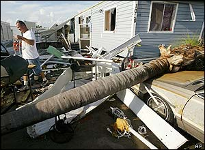 Duane West searches for items in front of his home in Punta Gorda, Florida