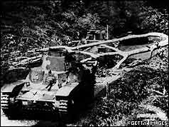 Two tanks one behind one in front of fallen tree