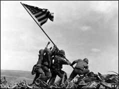 US Marines of the 28th Regiment of the 5th Division, raise the American flag atop Mt Suribachi,