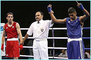 17-year-old Amir Khan (blue) defeats his Greek opponent in the first round of the boxing lightweight competition.
