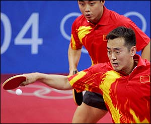 Linghui Kong smaches the ball as partner Hao Wang stands behind