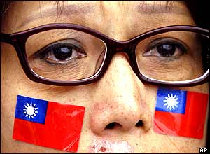 With Taiwanese flags stickers on her face, a protester listens intently to the speakers.