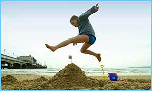 Boy jumping over a sandcastle on a beach