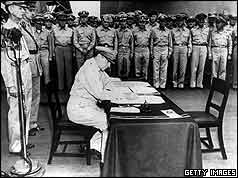 General MacArthur signing document at table with soldiers watching