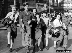 WAAFs link arms with soldiers during the VJ Day celebrations in Piccadilly Circus