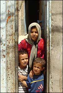 Children peer out from a house in Najaf