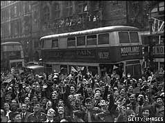 Crowds in front of double-decker bus